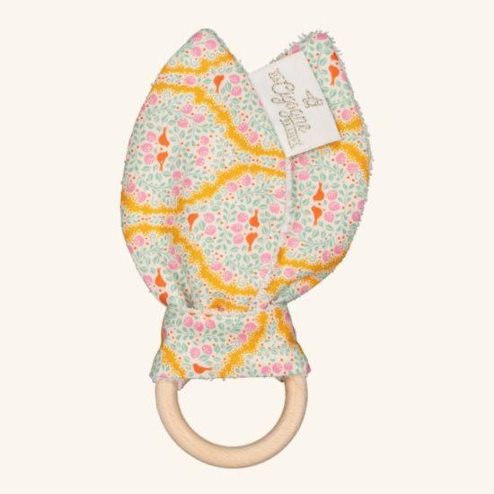 Un anneau de dentition en bois naturel non traité orné d'un joli tissu à motifs et d'un côté éponge pour les petites bavouilles de bébé.