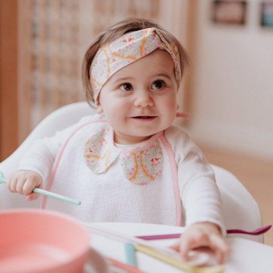 en tissu éponge blanc tout doux avec deux petits liens pour le nouer dans le cou de bébé.