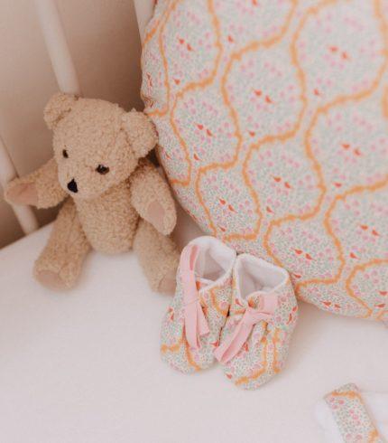 Des petits chaussons pour la maternité en tissu. On note le côté moelleux et douillet de ces petits chaussons